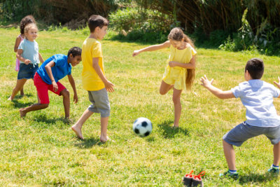 a group happy children playing football together