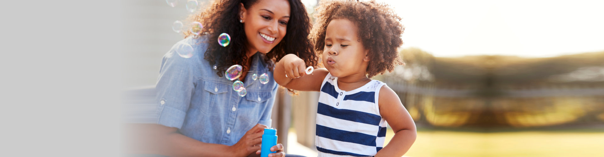 young woman looking a little girl blowing bubbles