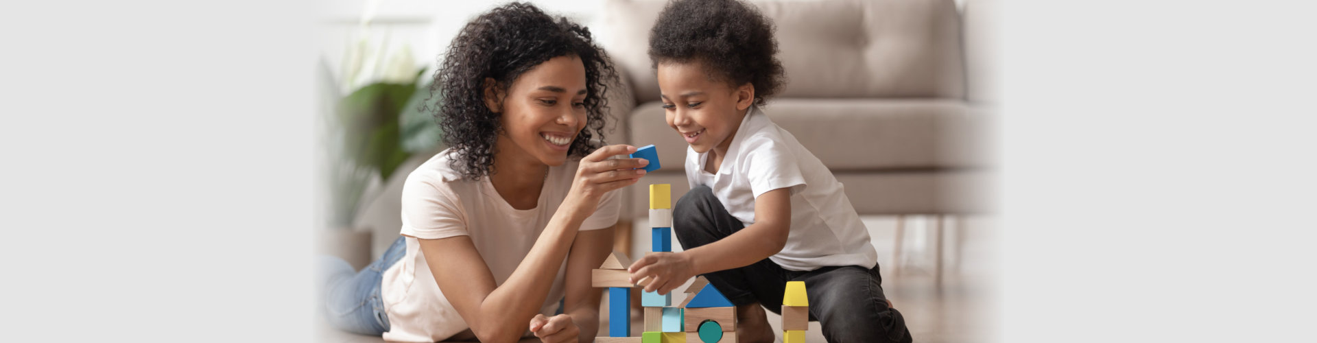 smiling woman assisting little boy play